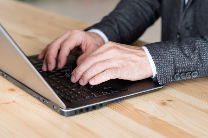 Computer portatile di battitura a macchina della mano dell'uomo lavoro a distanza affare online fotografie stock