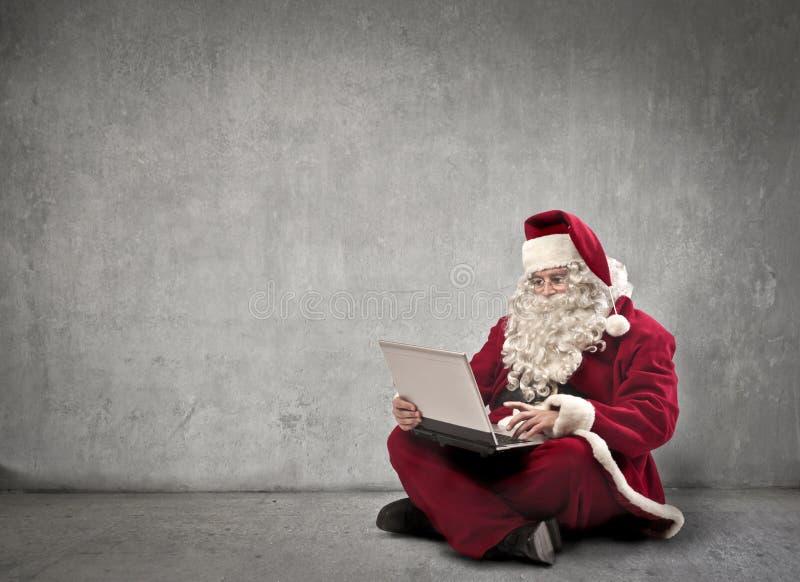 Computer portatile di buio del Babbo Natale immagini stock