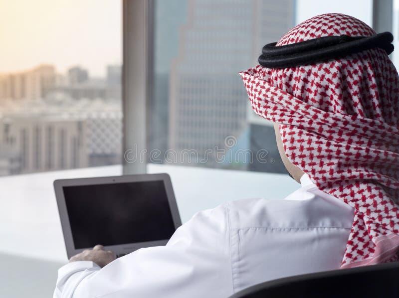 Computer portatile di sorveglianza dell'uomo saudita alla contemplazione del lavoro fotografia stock