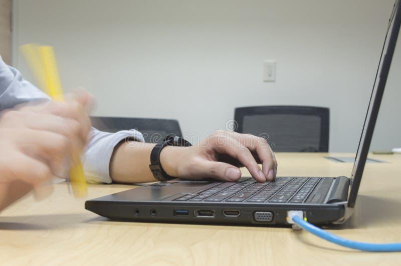Computer portatile di uso dell'uomo e penna di pensiero della tenuta sulla tavola di legno nella sala riunioni fotografia stock