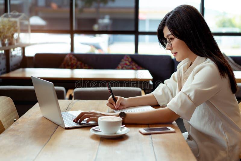 Computer portatile di uso della donna di affari ed indicare la bilancia dei redditi di piano fotografie stock libere da diritti