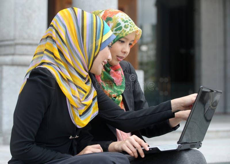 Una ragazza di due sciarpe che per mezzo del computer portatile fotografia stock libera da diritti