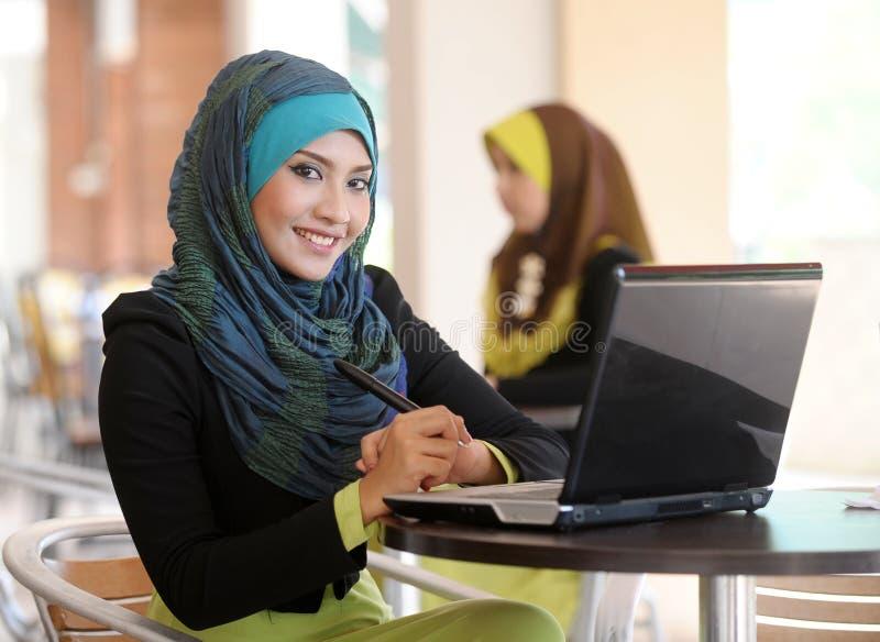 Una ragazza di due sciarpe che per mezzo del computer portatile immagine stock libera da diritti