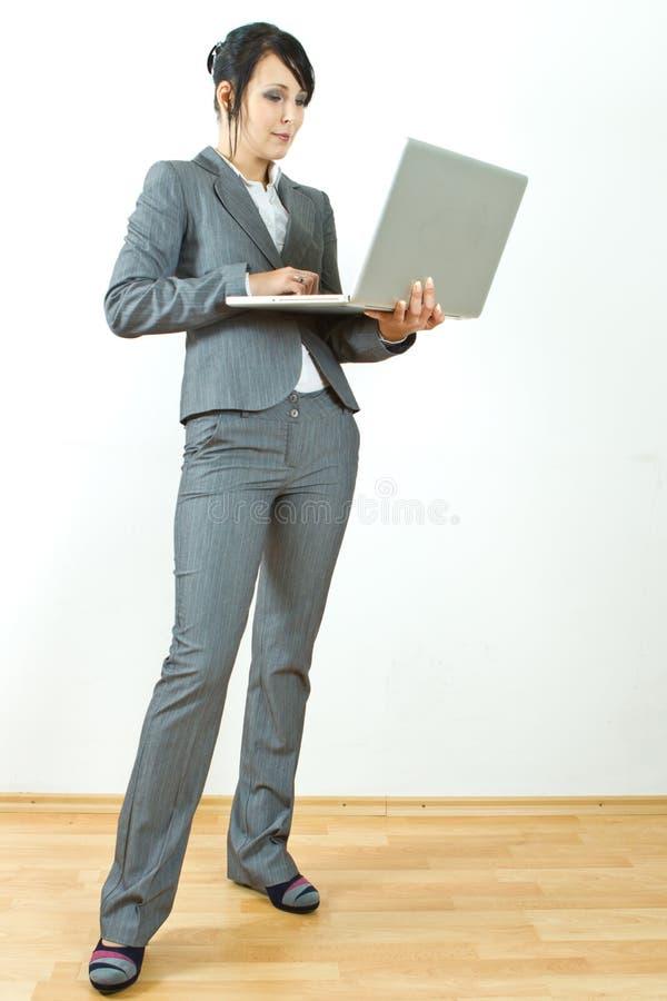 Computer portatile diritto della holding della donna di affari fotografia stock