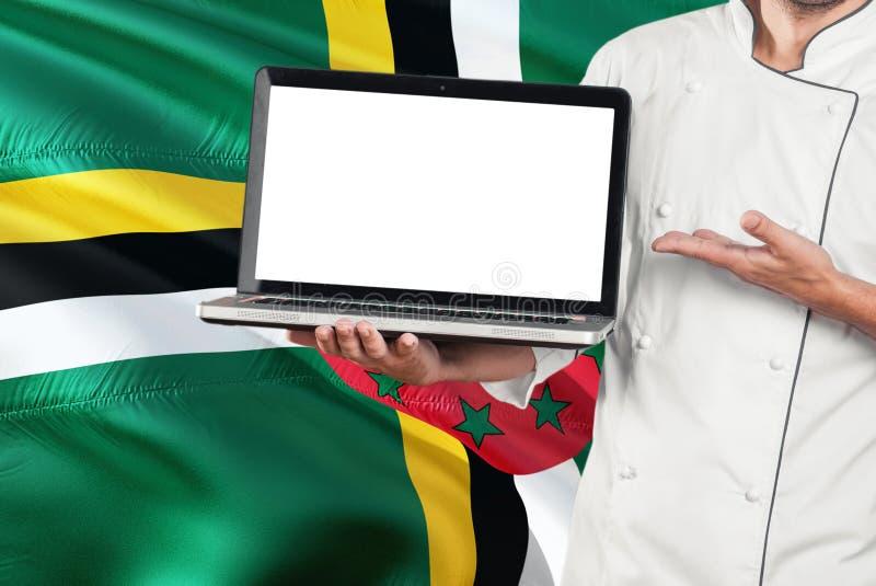 Computer portatile domenicano della tenuta del cuoco unico con lo schermo in bianco sul fondo della bandiera della Dominica Cucin immagine stock libera da diritti