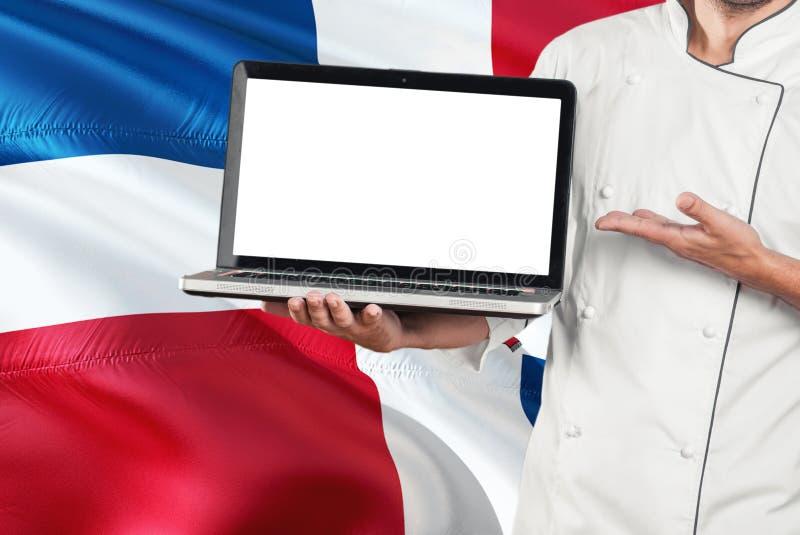 Computer portatile domenicano della tenuta del cuoco unico con lo schermo in bianco sul fondo della bandiera della Repubblica dom immagini stock libere da diritti