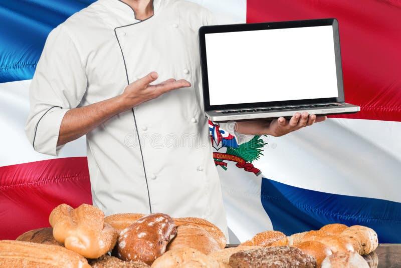 Computer portatile domenicano della tenuta del panettiere sulla bandiera della Repubblica dominicana e sul fondo dei pani Uniform fotografia stock