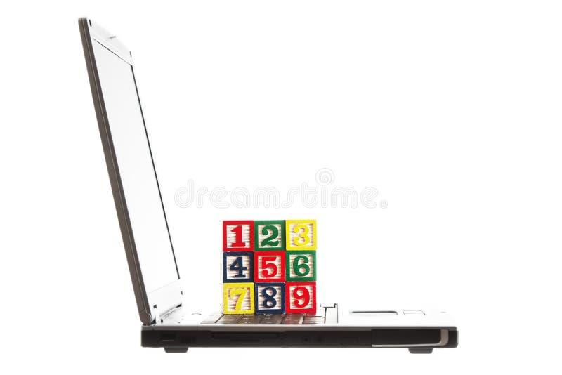 Computer portatile e blocchi di legno con i numeri isolati su bianco fotografia stock