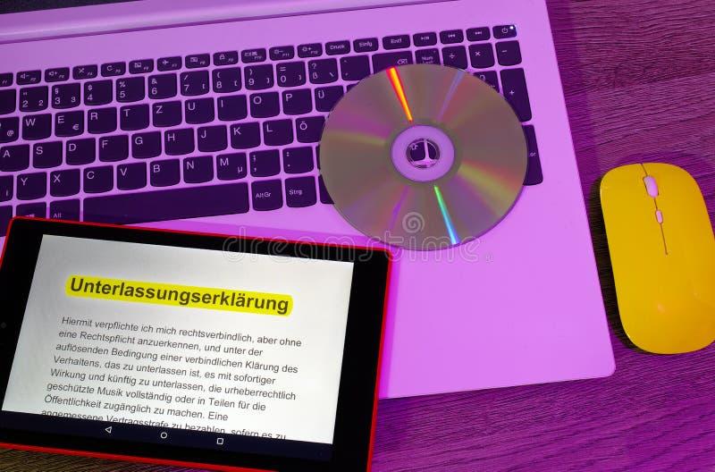 Computer portatile e compressa su cui un testo con una dichiarazione dell'omissione è visualizzato con il topo giallo nell'ottica immagini stock