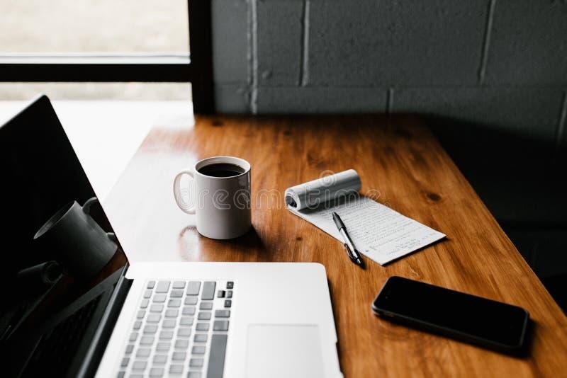 Computer portatile e telefono sulla scrivania immagini stock libere da diritti