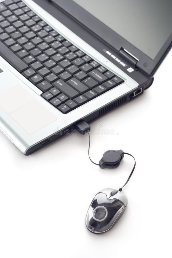 Computer portatile e un mouse immagine stock