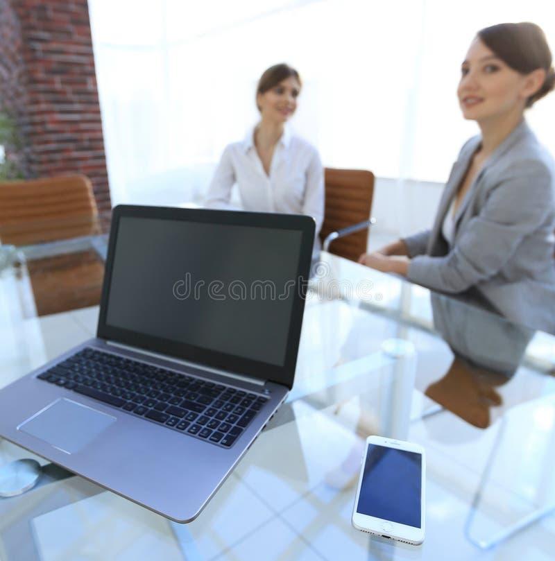 Computer portatile e uno smartphone sul desktop di un uomo d'affari immagini stock