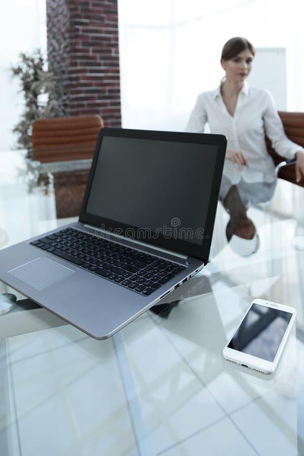 Computer portatile e uno smartphone sul desktop di un uomo d'affari fotografia stock