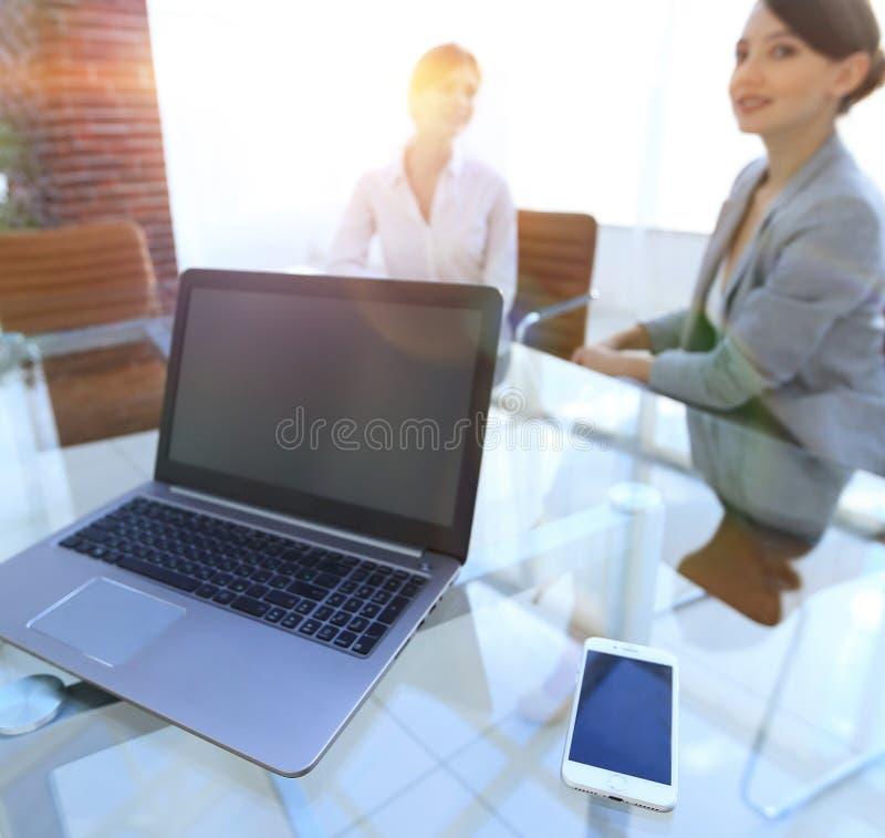 Computer portatile e uno smartphone sul desktop di un uomo d'affari immagine stock