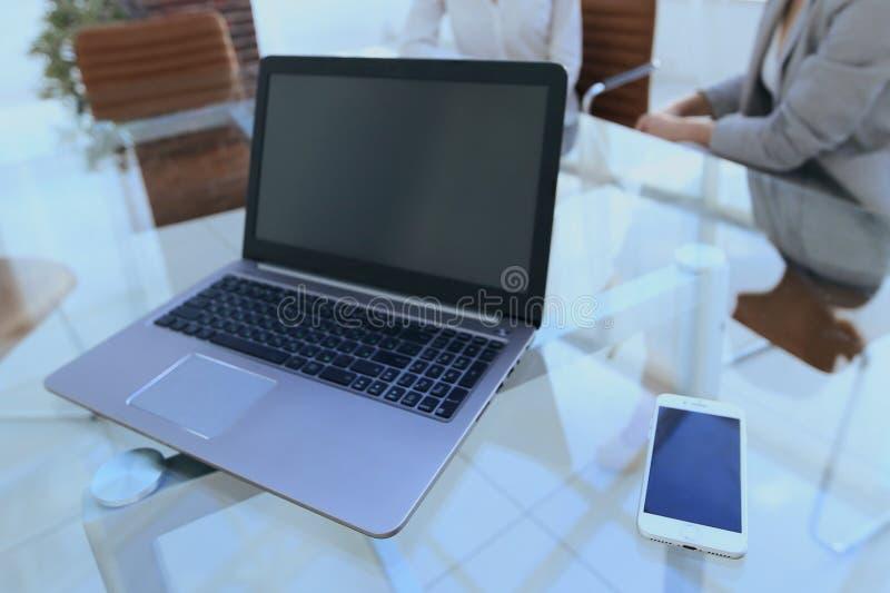 Computer portatile e uno smartphone sul desktop di un uomo d'affari fotografia stock libera da diritti