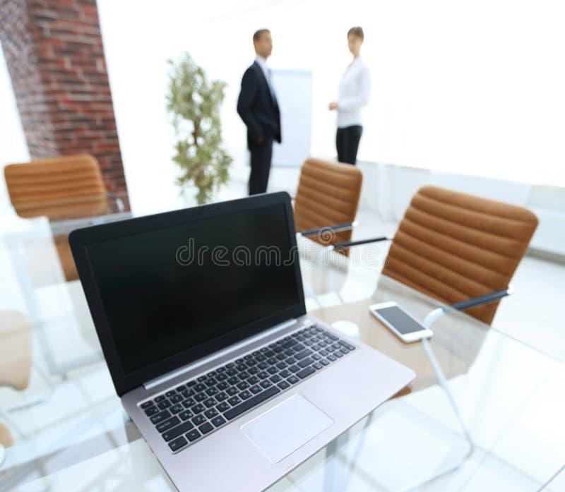 Computer portatile e uno smartphone sul desktop nell'auditorium immagini stock