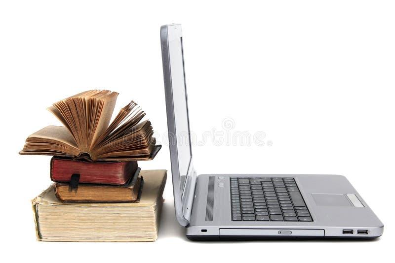 Computer portatile e vecchi libri fotografie stock