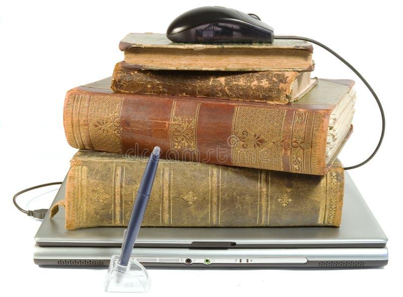 Computer portatile e vecchi libri con il percorso immagini stock libere da diritti