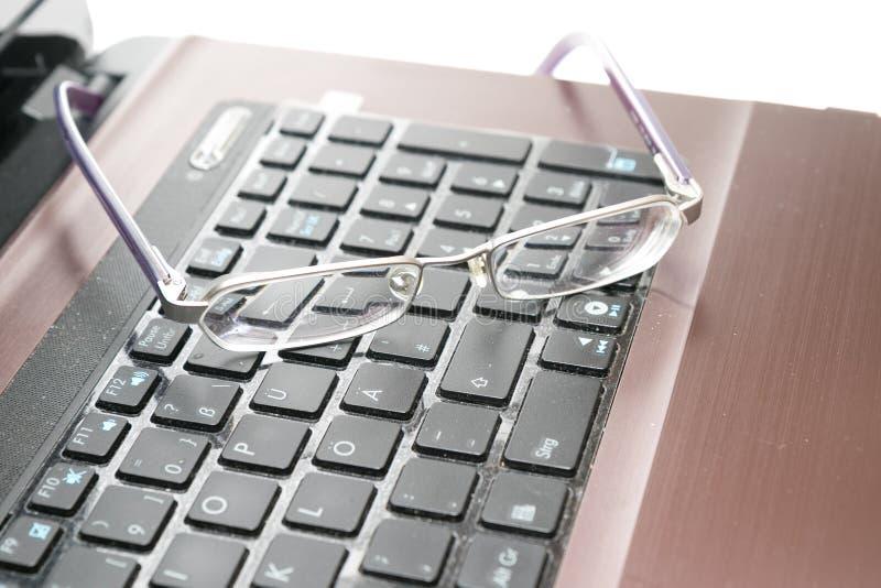 Computer portatile e vetri immagini stock
