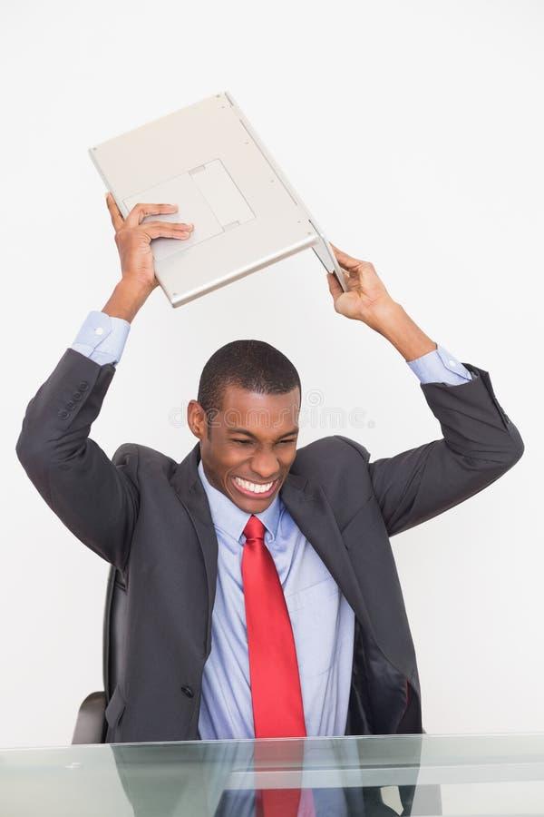 Computer portatile favoloso frustrato dell'uomo d'affari di afro sullo scrittorio fotografia stock libera da diritti