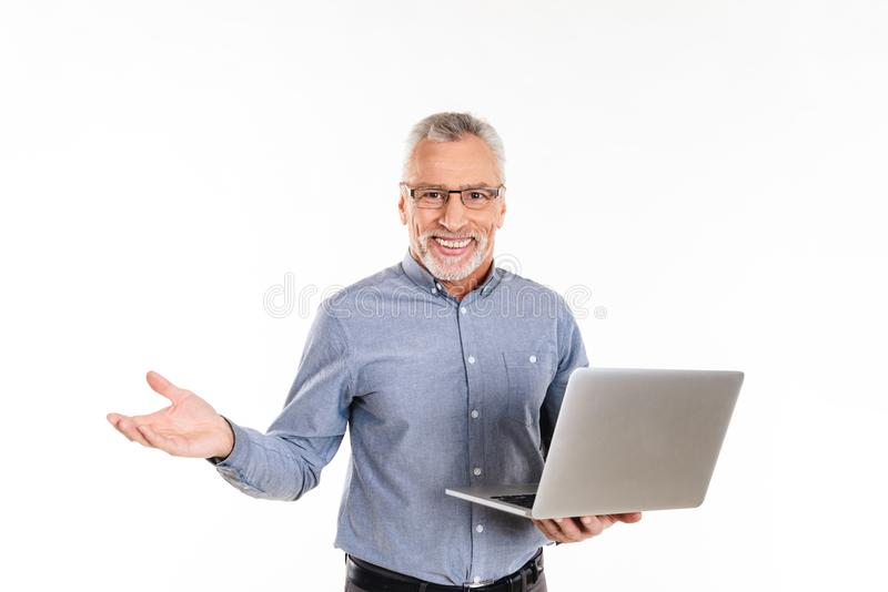 Computer portatile felice della tenuta dell'uomo e sorridere alla macchina fotografica isolata fotografia stock