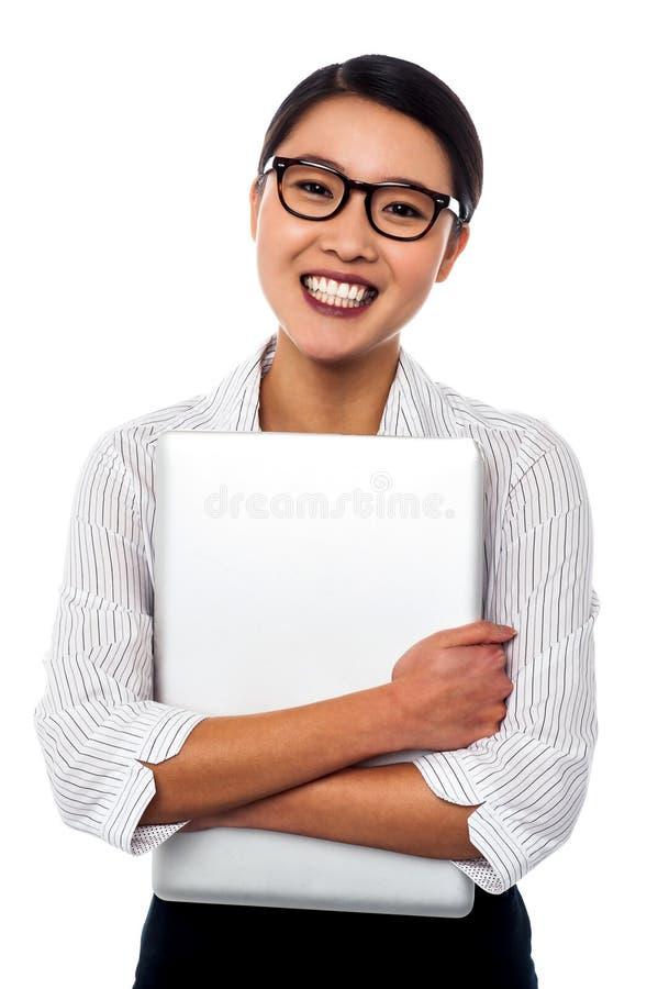 Computer portatile femminile della tenuta di segretario strettamente fotografia stock