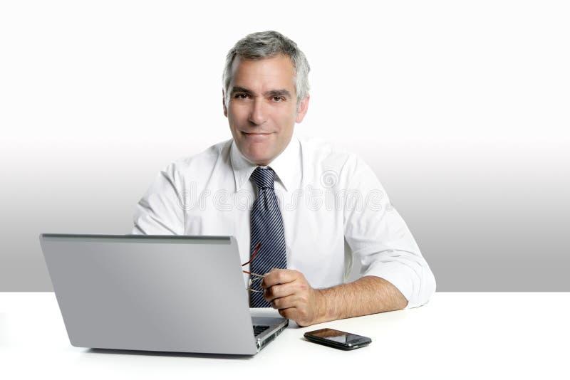 Computer portatile funzionante dei capelli grigi maggiori dell'uomo d'affari immagini stock