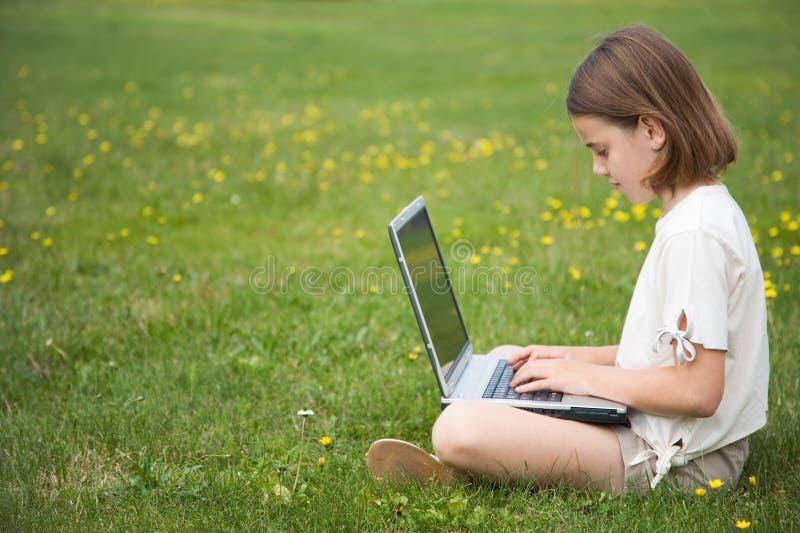 Computer portatile funzionante del bambino all'esterno immagine stock