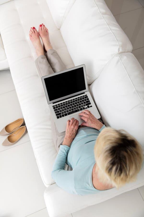 Computer portatile funzionante della donna fotografia stock