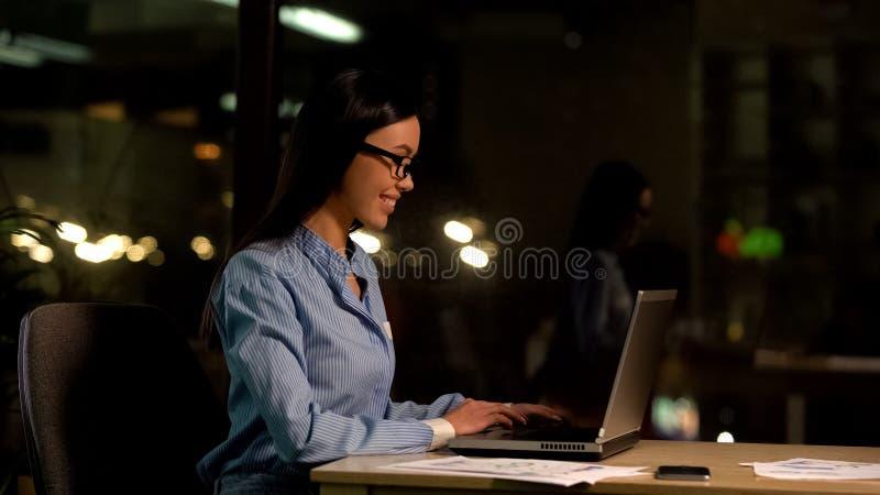 Computer portatile funzionante delle free lance felici alla notte, programma flessibile, impiegato produttivo fotografia stock libera da diritti