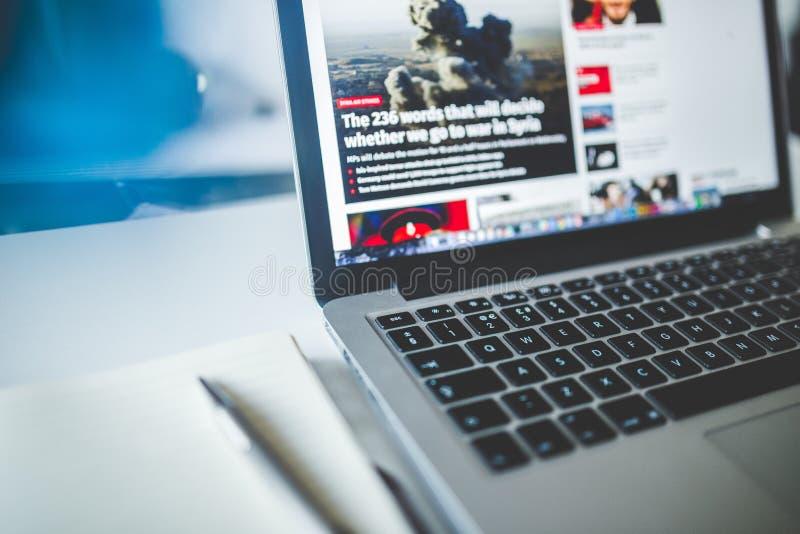 Computer portatile grigio vicino ai giornali immagine stock