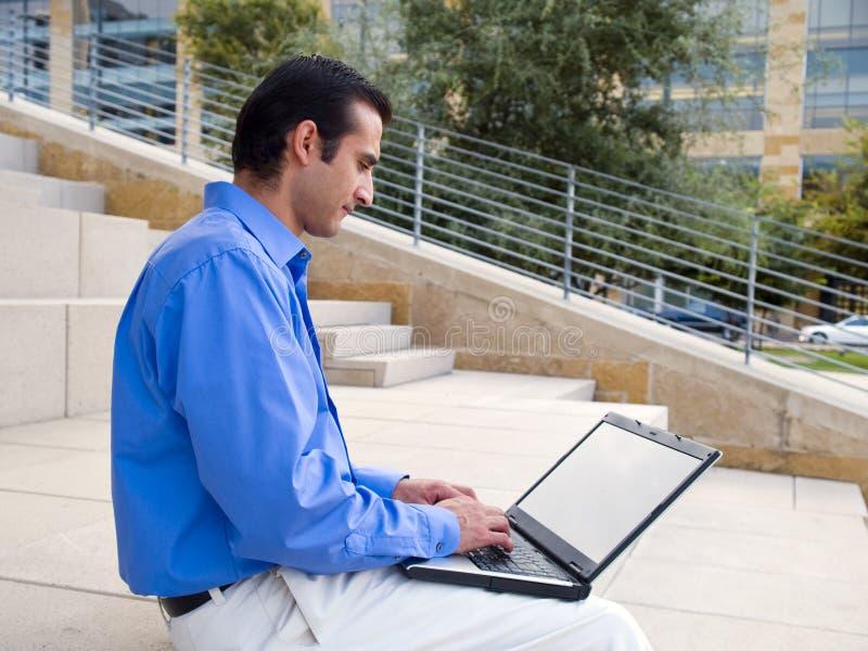 Computer portatile ispanico dell'uomo d'affari immagine stock