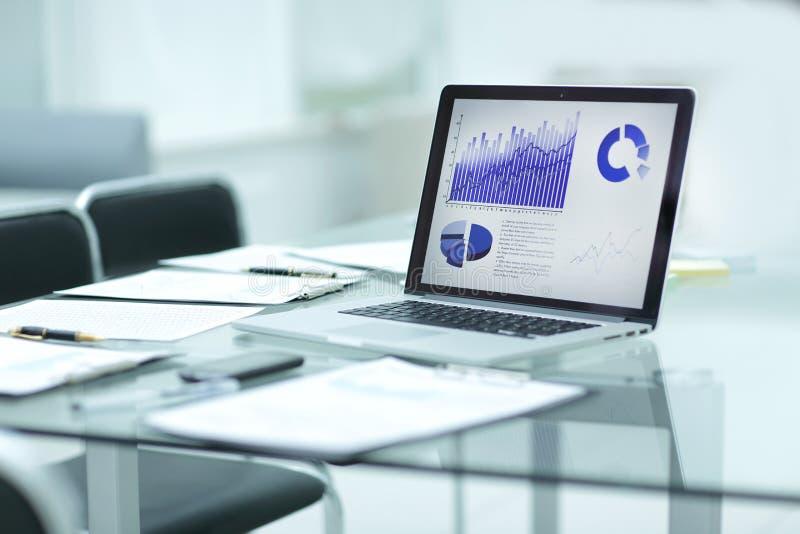 Computer portatile, lavagna per appunti e dati finanziari sullo scrittorio dell'uomo d'affari immagini stock libere da diritti