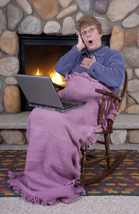 Computer portatile maggiore maturo di sorpresa di scossa della donna fotografie stock