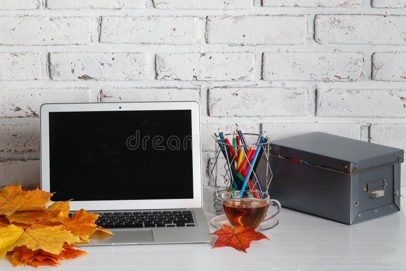 Computer portatile personale sulla tavola di legno sopra il fondo del muro di mattoni fotografia stock
