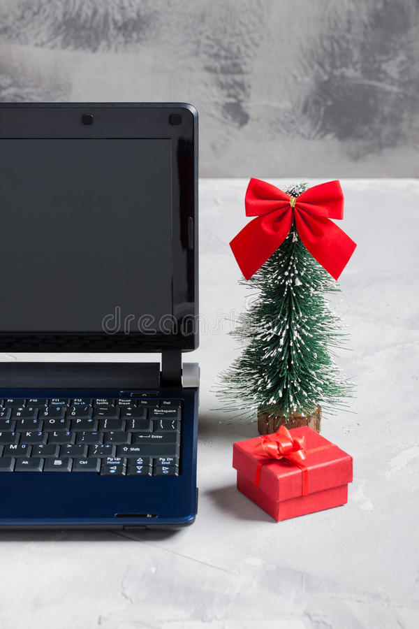 Computer portatile, poco albero di Natale e contenitore di regalo rosso fotografia stock libera da diritti