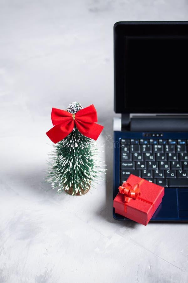 Computer portatile, poco albero di Natale e contenitore di regalo rosso immagini stock libere da diritti
