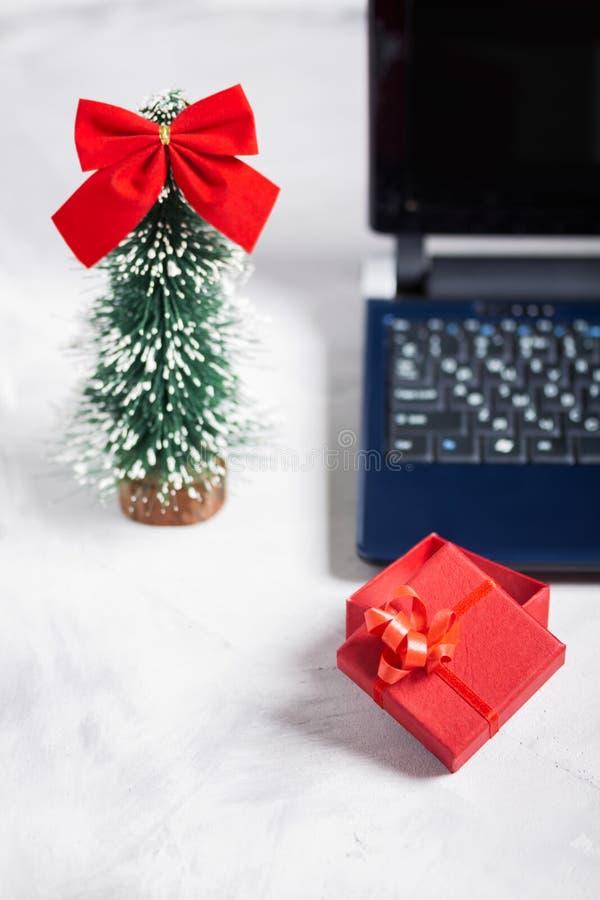 Computer portatile, poco albero di Natale e contenitore di regalo rosso immagine stock libera da diritti