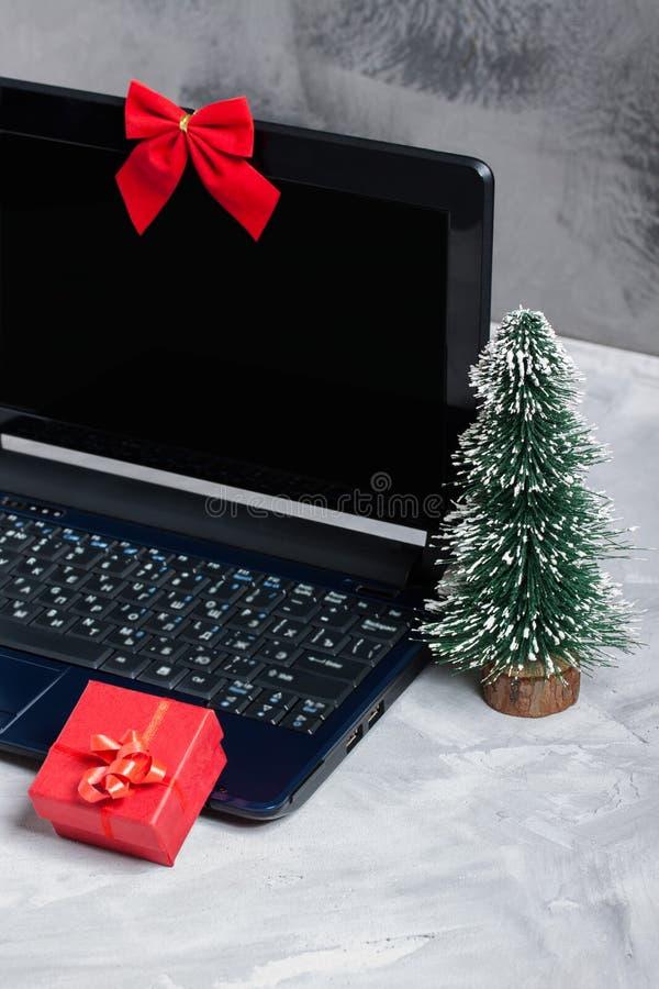 Computer portatile, poco albero di Natale e contenitore di regalo rosso fotografia stock