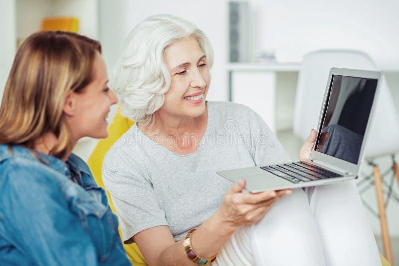 Computer portatile senior contentissimo allegro della tenuta della donna immagine stock