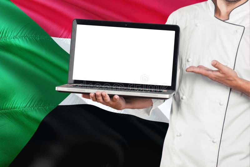 Computer portatile sudanese della tenuta del cuoco unico con lo schermo in bianco sul fondo della bandiera del Sudan Cucini l'uni immagini stock