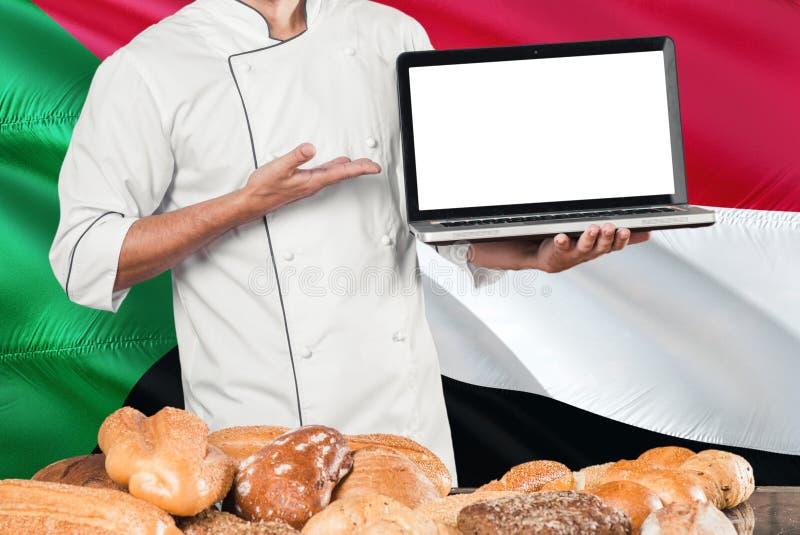 Computer portatile sudanese della tenuta del panettiere sulla bandiera del Sudan e sul fondo dei pani Uniforme d'uso del cuoco un fotografie stock libere da diritti
