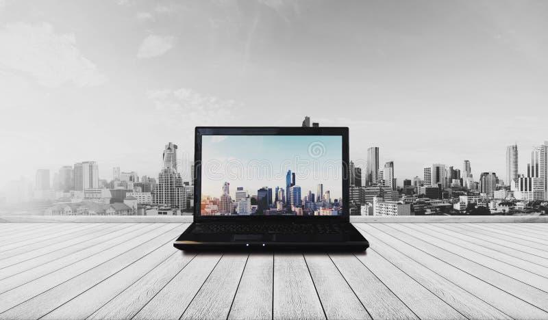 Computer portatile sul pavimento di legno con la visualizzazione moderna della città fotografie stock libere da diritti