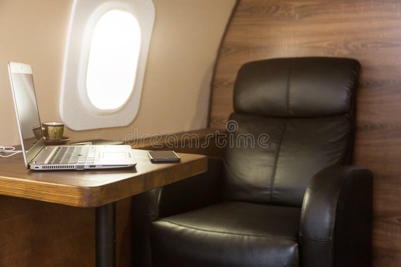 Computer portatile sulla tavola all'interno di un getto privato Primo codice categoria volante fotografia stock libera da diritti