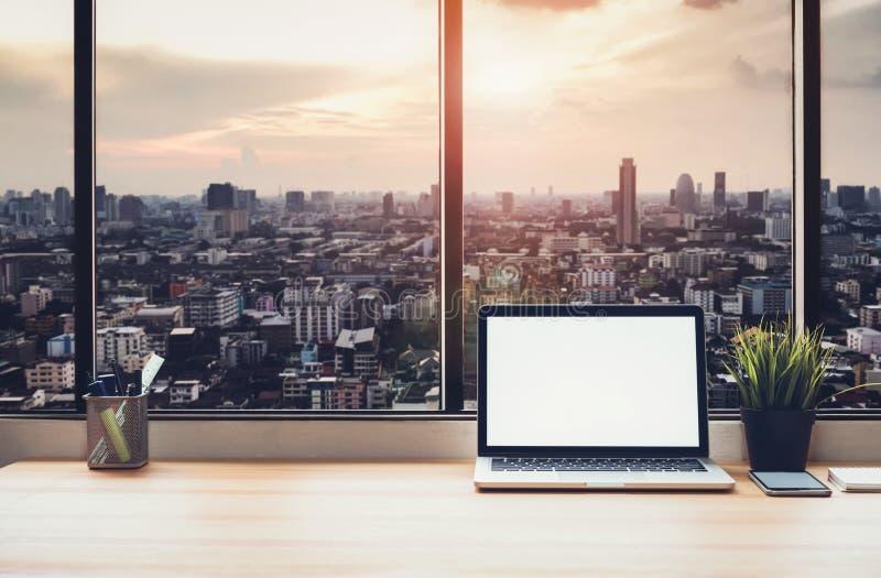Computer portatile sulla tavola nella stanza dell'ufficio sul fondo della città della finestra, per il montaggio del dispositivo  fotografia stock
