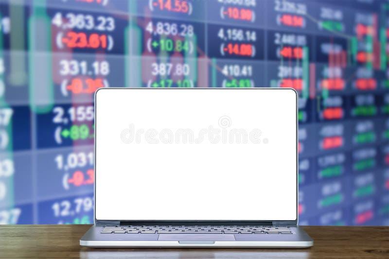 Computer portatile sullo scrittorio di legno con doppia esposizione del fondo del grafico del mercato azionario e dei dati di ris immagine stock