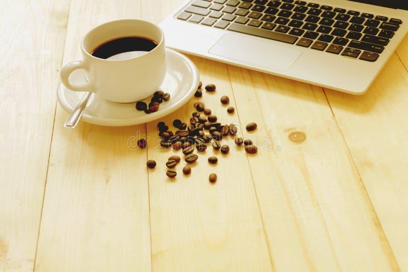 Computer portatile, tazza di caffè fresco e caffè fotografia stock