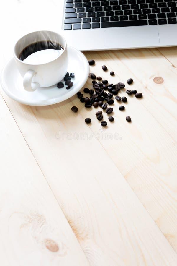 Computer portatile, tazza di caffè fresco e caffè fotografia stock libera da diritti