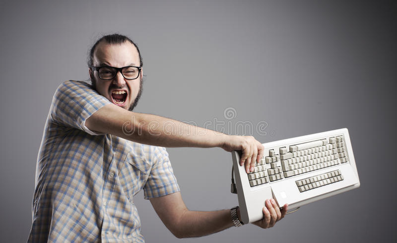 Computer problems. Angry man is destroying a keyboard royalty free stock photo