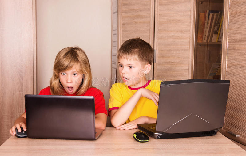 Computer problems. Stressed frustrated and scared children having computer problems. Cute girl and boy using laptops at home. royalty free stock photography